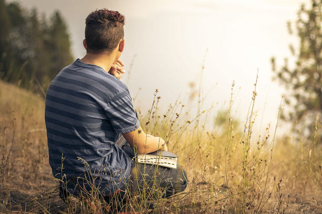 Boy kneeling outside with his bible