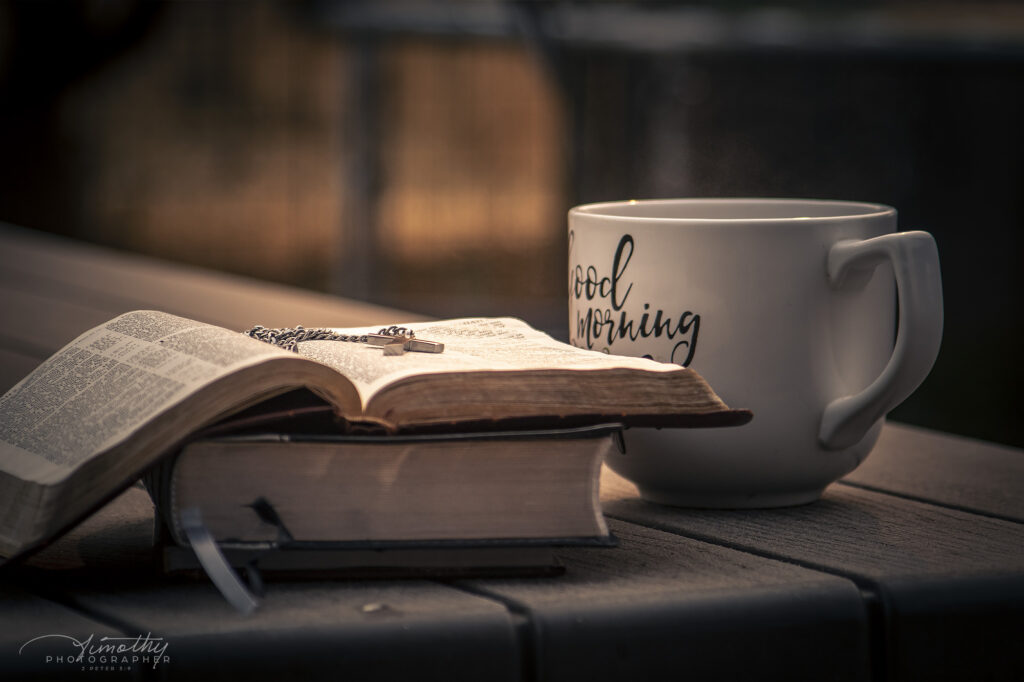 picture of a bible outside with a cross and fall leaves and cup of coffee