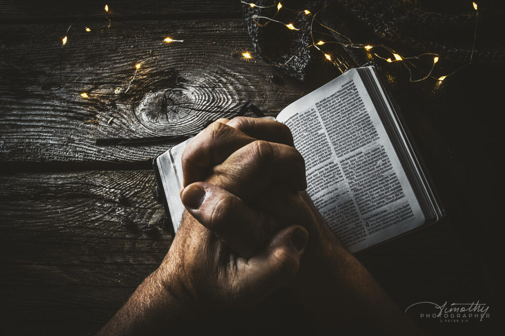 Praying hands over a bible